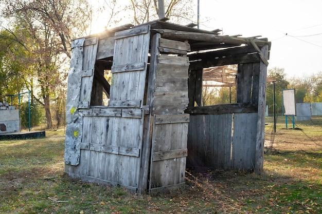 Un capannone di legno traballante di vecchie tavole con macchie di vernice gialla sull'erba nella foresta
