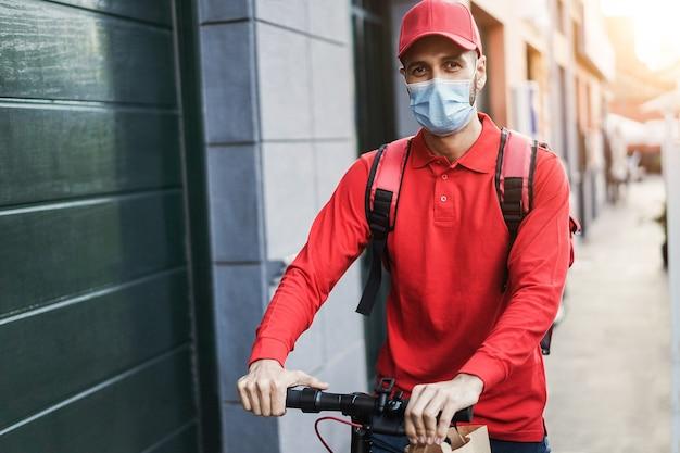 Rider che consegna il pasto con lo scooter elettrico mentre indossa la maschera protettiva - focus sul volto dell'uomo