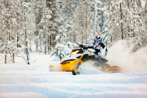 Il pilota alla deriva su una motoslitta su una superficie di neve profonda nella foresta invernale