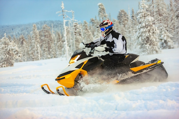 Il pilota in marcia con un casco alla deriva su una motoslitta su una superficie di neve profonda su uno sfondo di natura paesaggistica innevata e foresta invernale.