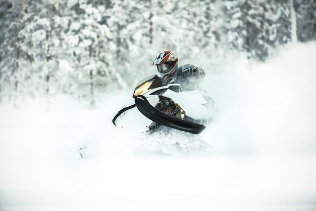 Il pilota in marcia con un casco alla guida di una motoslitta su una neve profonda