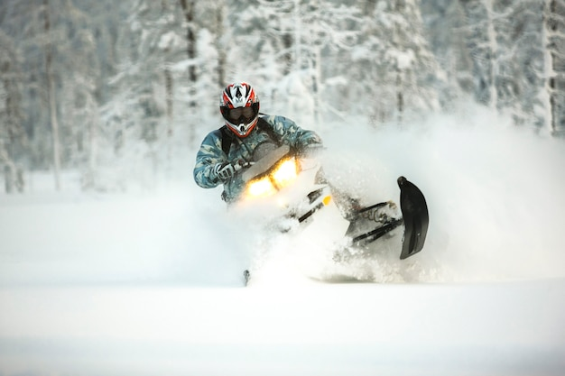 Il pilota in marcia con un casco fa una brusca svolta su una motoslitta su una vista frontale di neve profonda