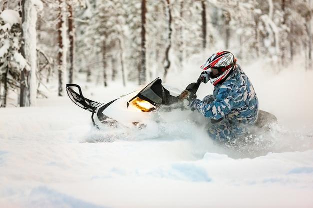 Il pilota in marcia con un casco fa una brusca svolta su una motoslitta su una neve profonda
