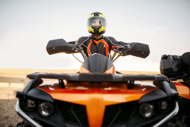 Pilota in casco e attrezzatura su quad, vista frontale, primo piano. pilota di quadbike maschio, guida atv