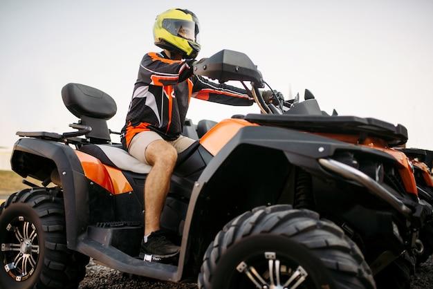 Pilota in casco su moto quad, vista frontale, primo piano