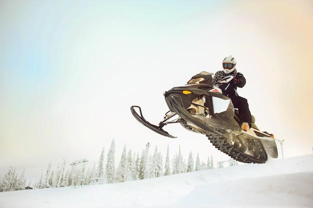 Il pilota che fa il salto volante decollando su una motoslitta su uno sfondo invernale