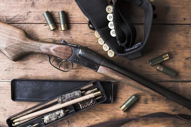 Fucile con prodotti per la pulizia su fondo di legno rustico