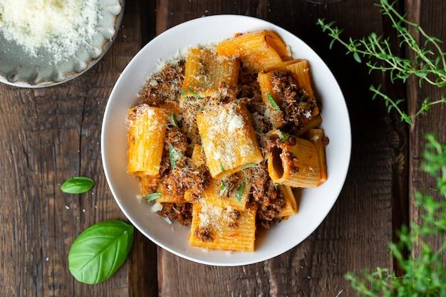 Rigatoni pasta con ragù ragù alla bolognese, parmigiano e basilico