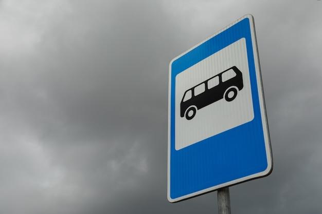 Roadsign blu e bianco ad angolo retto della fermata dell'autobus contro il cielo nuvoloso tenebroso