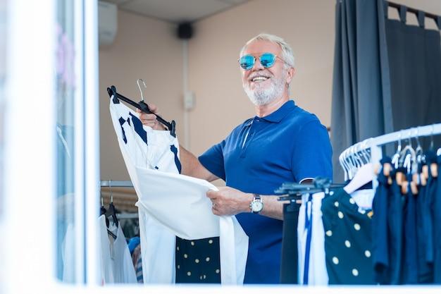 Giusta scelta. vita del cliente anziano positivo emotivo che tiene i pantaloni nelle mani mentre esprime la luminosità sul suo viso