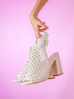 La mano destra tiene un paio di scarpe di moda estiva con tacchi alti su un muro rosa. scarpe estive in pelle da donna.