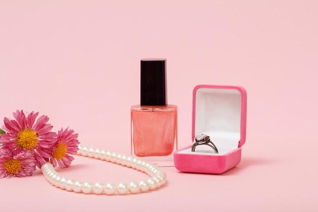 Anello in una scatola, smalto per unghie, perline su una corda in uno sfondo rosa. gioielli, cosmetici e accessori da donna.