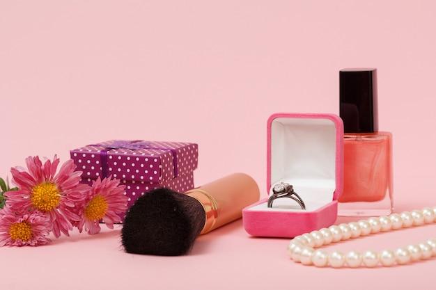 Anello in una scatola, smalto per unghie, pennello, perline, confezione regalo e fiori su uno sfondo rosa. gioielli, cosmetici e accessori da donna.