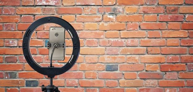 Lampada ad anello e uno smartphone contro il muro