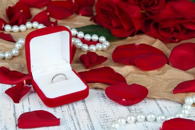 Anello circondato da rose e petali sul primo piano del tavolo in legno
