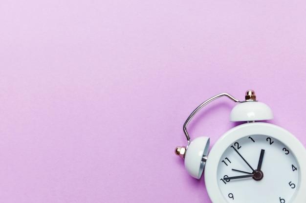 Suonare la sveglia classica vintage campana gemella isolata sul pastello viola viola colorato