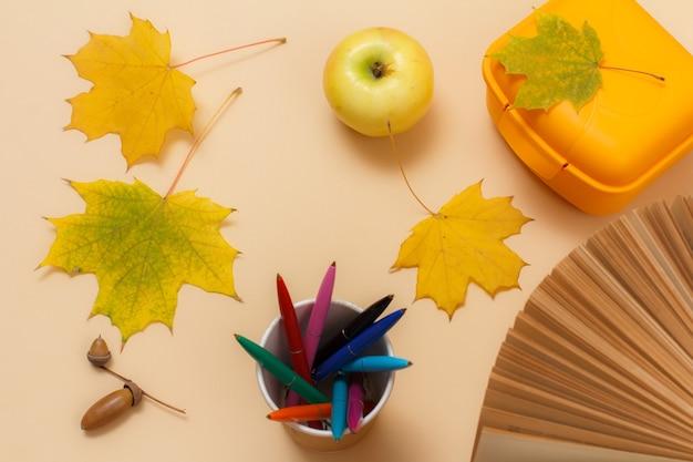 Mela matura, un libro, un cestino per il pranzo di plastica, penne, foglie di acero gialle secche e una ghianda sulla superficie beige