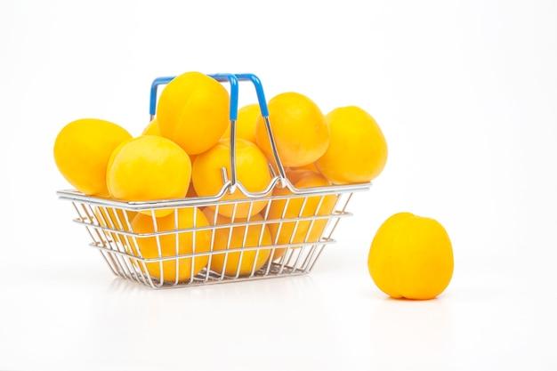 Albicocche mature in un cesto della spesa da un supermercato su sfondo bianco