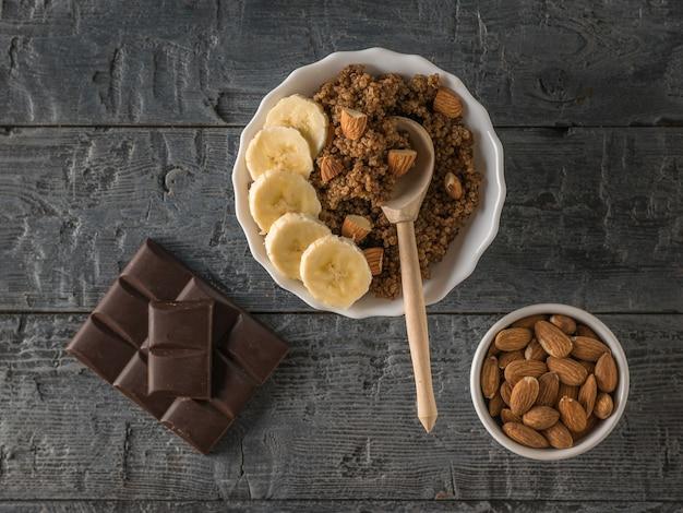 Banana matura, mandorle e porridge di quinoa con cacao su un tavolo rustico. dieta sana. disposizione piatta.