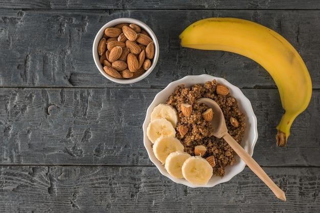 Banana matura, mandorle e porridge di quinoa con cacao su un tavolo di legno. dieta sana. disposizione piatta.