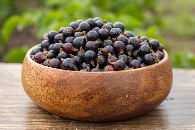 Ribes nero maturo in un piatto di legno su un tavolo in giardino. avvicinamento