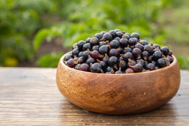 Ribes nero maturo in un piatto di legno su un tavolo in giardino. copia spazio