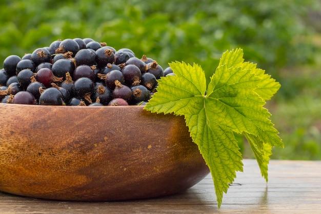 Ribes nero maturo in un piatto di legno con un foglio, su un tavolo in giardino