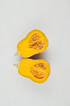 Zucca butternut matura tagliata in due su sfondo grigio chiaro. raccolto, mangiare sano e concetto di cucina