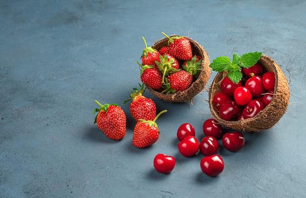 Ciliegie mature e fragole in gusci di cocco su uno sfondo scuro. vista laterale, copia dello spazio. frutti e bacche estive.