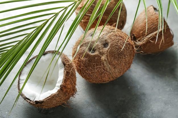 Noci di cocco mature e foglia di palma sul tavolo grigio