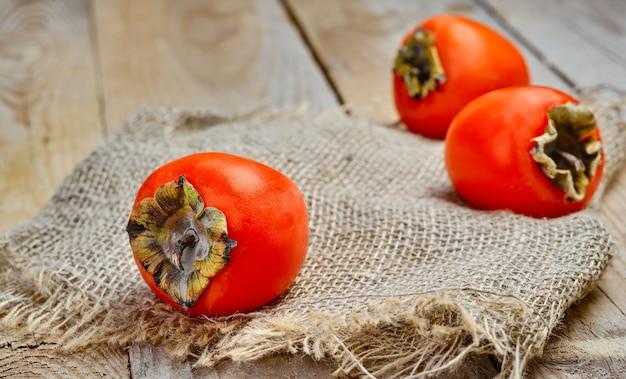Cachi arancioni deliziosi maturi. cachi freschi su una stuoia stuoia, primo piano. tavolo rustico in legno, telaio orizzontale.