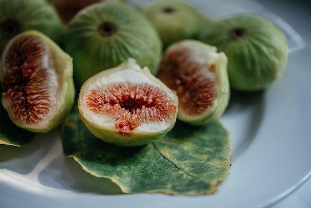 Frutti e foglie freschi maturi del fico su fondo bianco