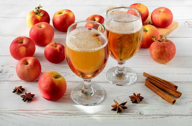Mele rosse succose fresche mature, spezie e bicchieri con sidro su una superficie in legno chiaro.