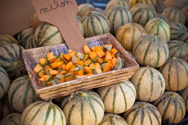 Meloni freschi maturi si accumulano in un mercato degli agricoltori