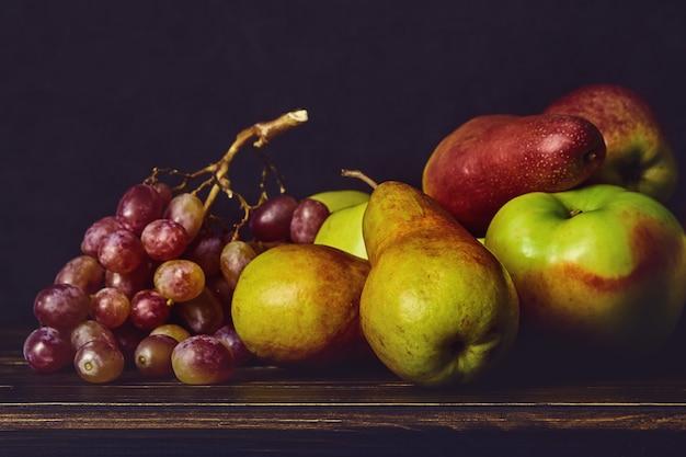 Frutti maturi, mele, pere, uva su un vecchio tavolo in legno e uno sfondo scuro.