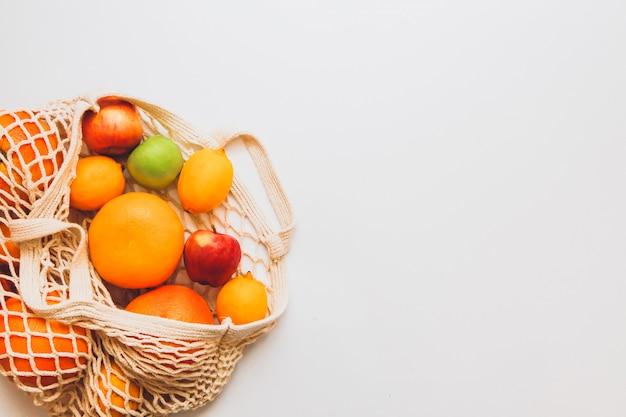 Frutti maturi nella borsa a rete all'uncinetto sullo spazio bianco. concetto di stile di vita sano. concetto di consegna.
