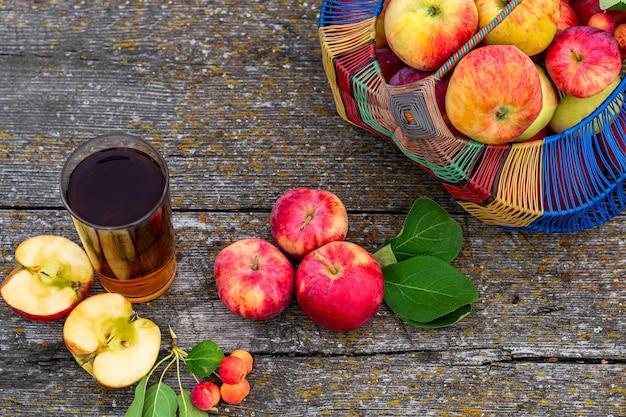 Mele mature del giardino in un canestro su un succo di mela appena spremuto di legno in uno stile rustico di vetro