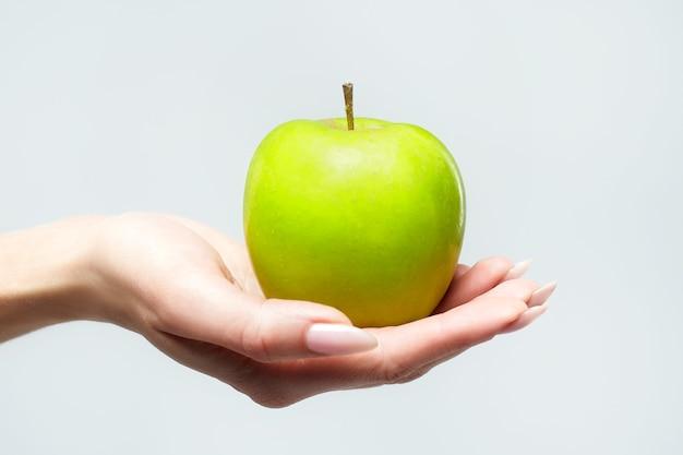Una mela verde matura nel palmo della mano di una giovane donna