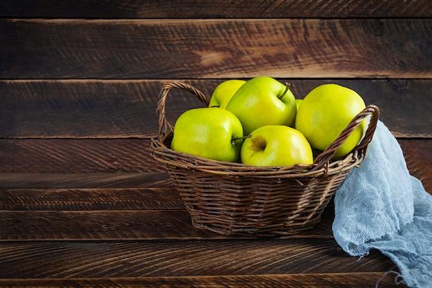 Mele verdi mature su uno sfondo di legno. deliziose mele succose