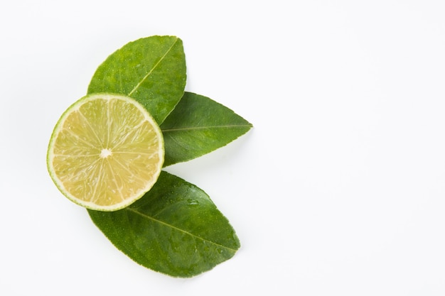 Frutta matura del limone verde su superficie bianca.