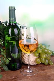 Merce nel carrello verde e porpora matura dell'uva con vino sulla tavola di legno su fondo luminoso