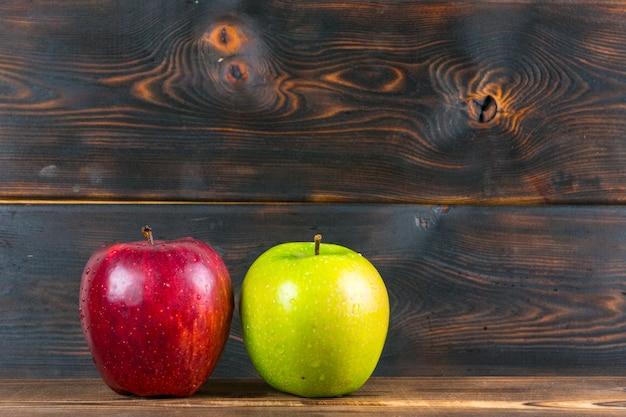 Mele rosse e verdi succose mature sulla tavola di legno rustica