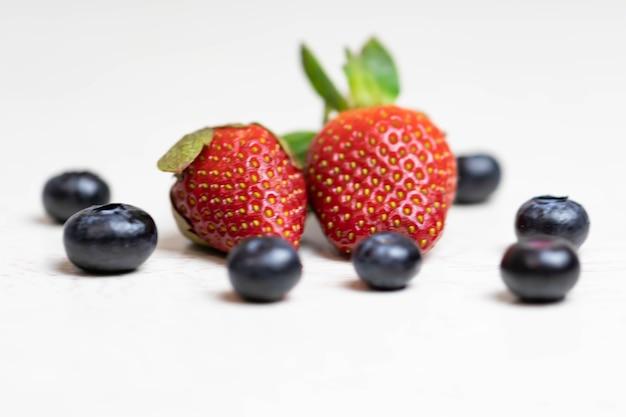 Fragole e mirtilli maturi e succosi su sfondo bianco. mangiare sano.