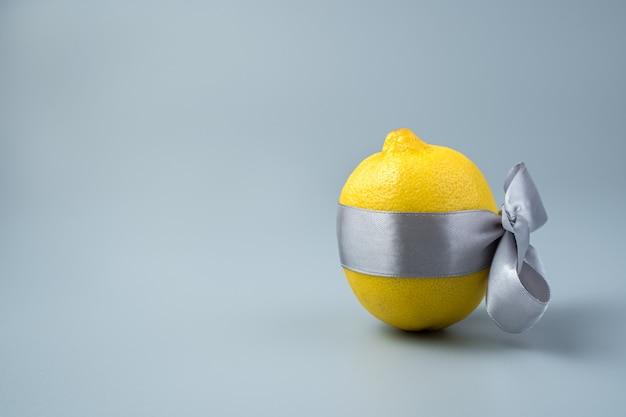 Limone maturo in un nastro di raso con un fiocco su uno sfondo grigio.