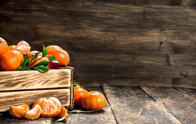 Mandarini maturi in una vecchia scatola sulla tavola di legno.