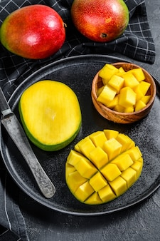 Un mango maturo. tagliare a cubetti di frutta tropicale. sfondo nero. vista dall'alto