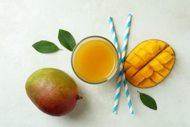 Frutta e succo di mango maturi sul tavolo bianco