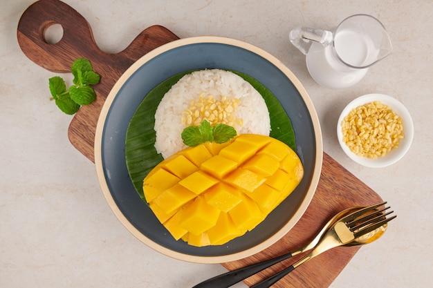 Mango maturo e riso appiccicoso con latte di cocco in un piatto sulla superficie di pietra, dessert dolce tailandese nella stagione estiva.