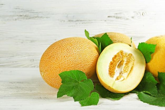 Meloni maturi con foglie verdi sul tavolo di legno