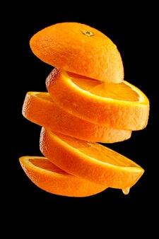 Arancia matura tagliata a fette e lanciata nell'aria isolata sul nero